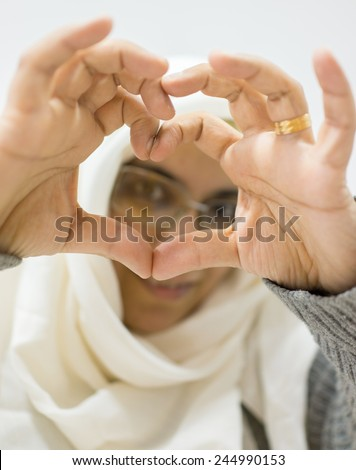 Muslim Arabic woman with heart shaped love symbol hands - stock photo
