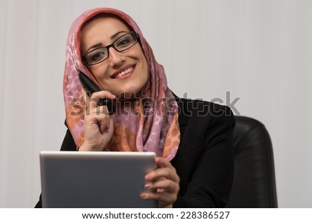 Muslim Business Woman Working At Her Computer While Talking On The Phone - stock photo
