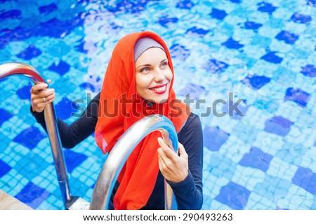 muslim caucasian woman entering a swimming pool - stock photo