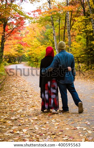 Muslim couple with colourful trees as background during autumn season - stock photo