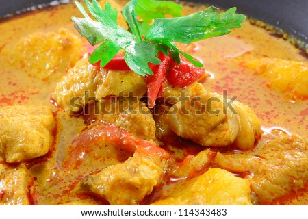 MUSLIM CURRY WITH CHICKEN TOPPING WITH PARSLEY AND CHILI IN BLACK BOWL - stock photo
