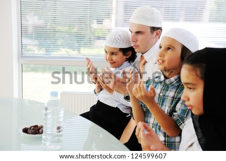 Muslim father praying with kids for Ramadan - stock photo