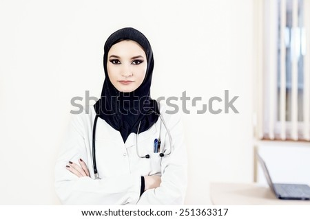 Muslim female doctor standing with hands crossed against the wall - stock photo
