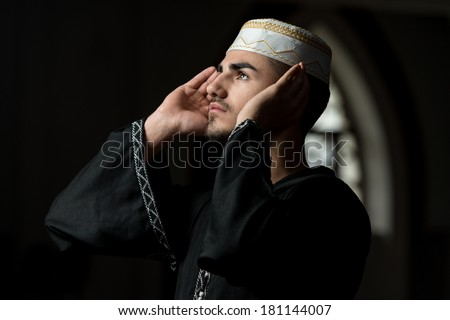 Muslim Man Is Praying In The Mosque - Guy Making Traditional Prayer To God While Wearing A Traditional Cap Dishdasha - stock photo