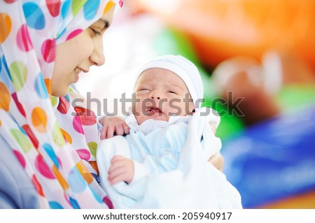 Muslim mom with newborn baby several days old enjoying new life - stock photo