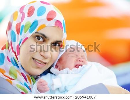 Muslim mom with newborn baby several days old enjoying new life - stock photo