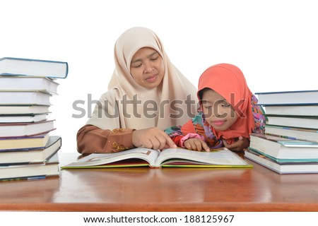 Muslim Mother and daughter looks in book in table - stock photo
