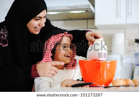 Muslim mother and little son in the kitchen - stock photo
