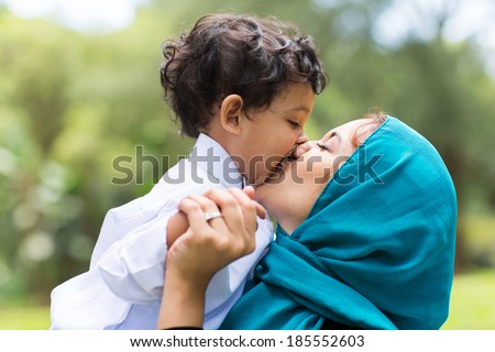 muslim mother kissing her baby boy close up - stock photo