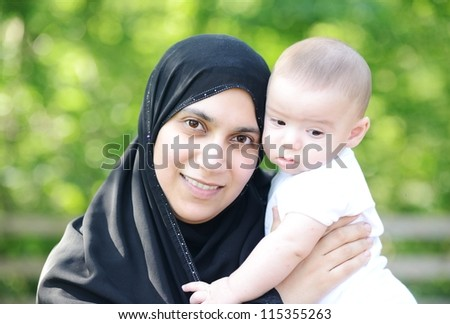 Muslim mother with her baby in green nature - stock photo
