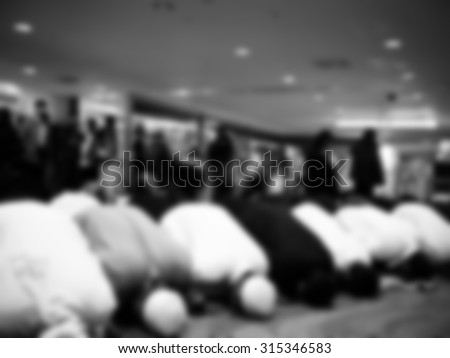 Muslim pilgrim pray in airport during their transit to Mecca, KSA to perform Hajj Blurred background in black and white - stock photo