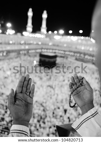 Muslim praying at Makkah holy Islamic place - Kaaba is visible - stock photo