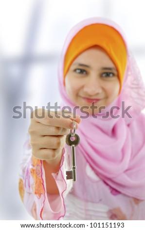 Muslim woman holding a new key - stock photo