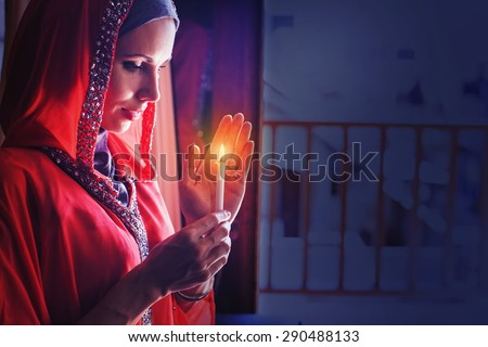 muslim woman holding candle in a ramadan night - stock photo