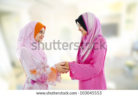 Muslim woman in traditional clothing greeting to each other, indoor. - stock photo