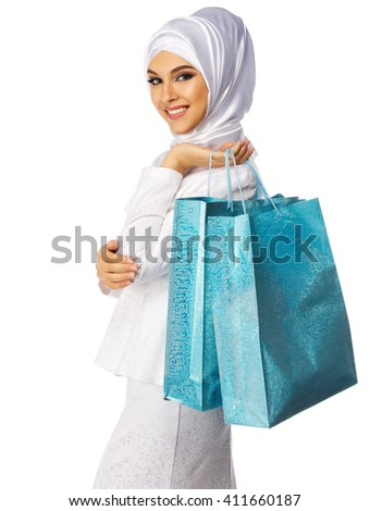 Muslim woman in white dress with bags isolated - stock photo