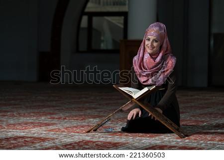 Muslim Woman Reading The Koran - stock photo