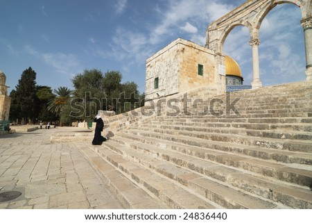 Muslim woman walking down the stairs of the Dome of the Rock in Jerusalem - stock photo