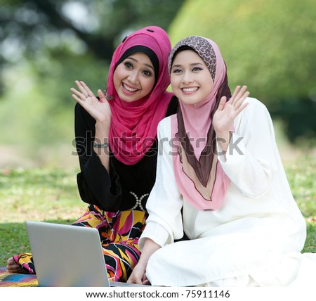 Muslim young woman in head scarf say bye to they friends - stock photo
