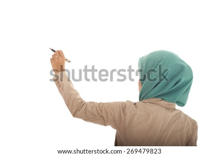 Muslimah woman writing on blank wall. - stock photo