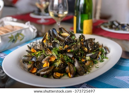 Mussels in a porcelain plate on a table against the background of a bottle of wine - stock photo