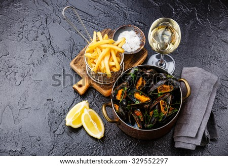 Mussels in copper cooking dish with wine and french fries on black stone background - stock photo