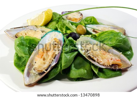 mussels under cheese and salad served in the restaurant - stock photo