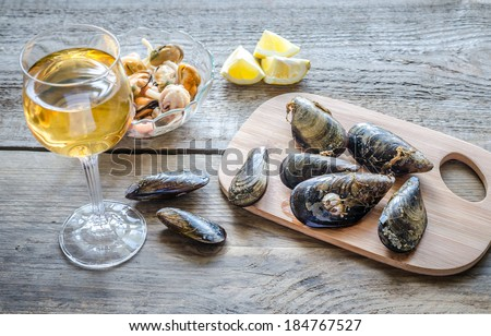 Mussels with a glass of white wine on the wooden table - stock photo