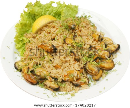 Mussels with rice, fresh herbs, lemon and green salad for a tasty seafood meal - stock photo
