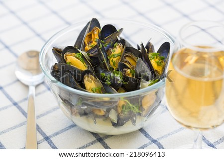 Mussels with white wine sauce in modern plate on table - stock photo