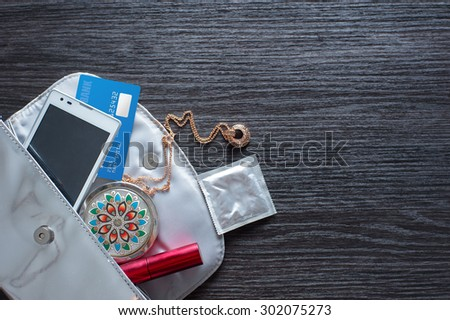 Must have for party night. Overhead of essentials for modern young woman. Different objects on wooden background: silver handbag with smartphone, bank card, little mirror and condom. - stock photo