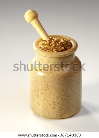 Mustard in a rustic potty with wooden spoon isolated on background  - stock photo