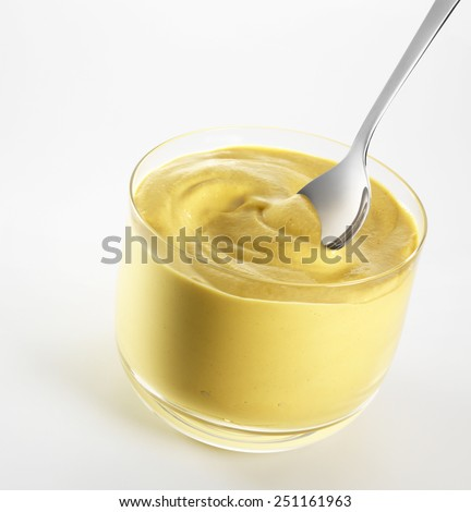 Mustard in glass bowl, with a little spoon, isolated on a white background - stock photo