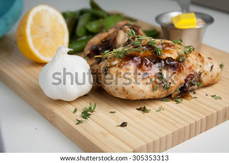 Mustard Maple glazed chicken on a cutting board with garlic, lemon, and snap peas - stock photo