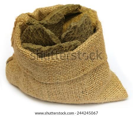Mustard oil cake in a sack bag over white backgroud - stock photo