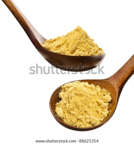 mustard powder in a wooden spoon  isolated over white - stock photo