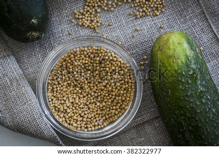 Mustard seeds and a cucumber. Ingredients for pickles - stock photo