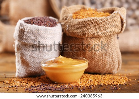 Mustard seeds in bags and sauce in bowl on  wooden background - stock photo