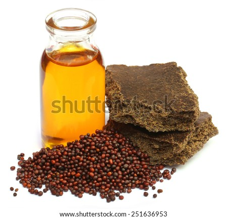 Mustard seeds oil and cake over white background - stock photo