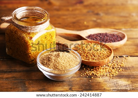 Mustard seeds, powder and sauce in glass jar, bowl and wooden spoons on wooden background - stock photo