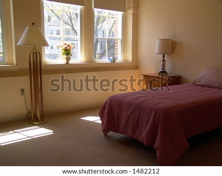 muted toned bedroom with sunlight shining through windows - stock photo