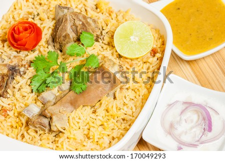 Mutton Biryani - Closeup view from the top of delicious mutton (lamb) biryani garnished with tomato peel, cilantro and lemon. It is served with onion salad (raita) and vegetable curry. - stock photo