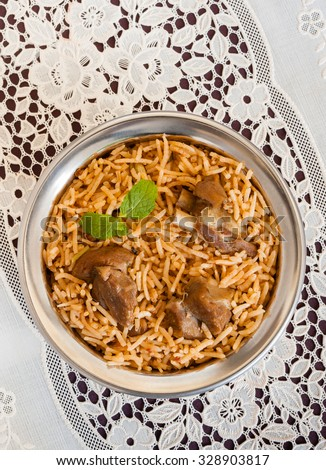 Mutton biryani overhead view - Overhead view from the top of delicious mutton (lamb) biryani with mint garnish and served in authentic copper bowl. Natural light used. - stock photo