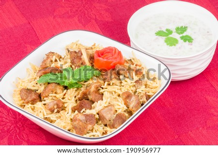 Mutton Biryani with Salad - Closeup view from the top of delicious mutton (lamb) biryani garnished with tomato peel and mint. Served with salad (raita). - stock photo