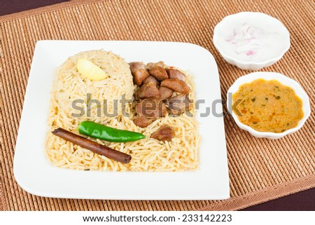 Mutton Biryani with Salad - Overhead view from the top of delicious mutton (lamb) biryani with garnish and served with salad (raita) and gravy. Innovative presentation. - stock photo