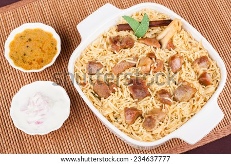 Mutton Biryani with Salad - Overhead view from the top of delicious mutton (lamb) biryani with garnish and served with salad (raita) and gravy. - stock photo