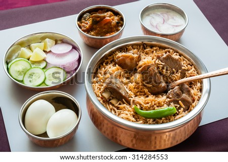 Mutton biryani with traditional sides - Closeup view from the top of delicious mutton (lamb) biryani served in authentic copper utensils with salad (raita), gravy and egg. Natural light used. - stock photo