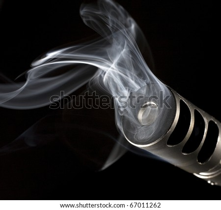 muzzle on a rifle that has smoke pouring out from it - stock photo