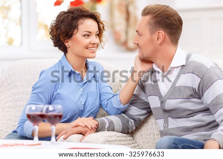 My darling. Pleasant sensitive young couple sitting in the armchair and holding hands of each other while expressing love - stock photo
