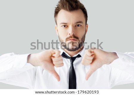 My decision. Portrait of confident young man in shirt and tie looking at camera and showing his thumbs down while standing against grey background - stock photo